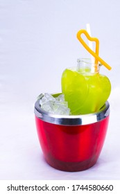 Apple Cocktail In a luxuriously shaped glass consisting of ice and sliced apples, decorated with green herbs Filmed on a white sce. Bottle, herb.