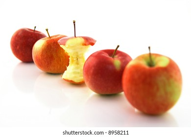 Apple core among whole apples, with focus on the core.