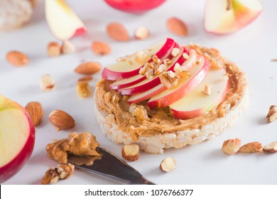 Apple crisp bread toast with apple slices, peanut butter, almonds and walnuts. Healthy breakfast concept in a high key.