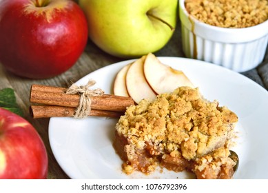 Apple crumble on white dish with spoon and fresh green and red apple with cinnamon stick on wooden floor. Easy and Basic dessert menu.