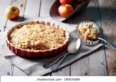 Apple crumble on the wooden background with apples .