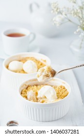 Apple crumble, spoon with ice cream, streusel. Side view, vertical. Morning breakfast on light gray table
