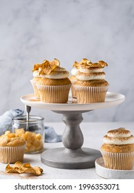 Apple cupcakes with cream cheese frosting decorated with dried apple slices and cinnamon powder. Autumn festive dessert. Homemade tasty pastry on ceramic cake plate. Close up food.