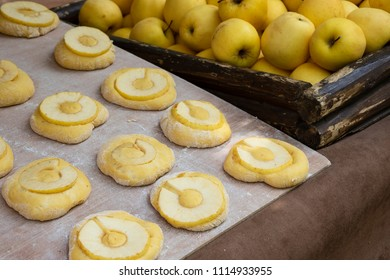 Apple donuts prepared for frying. Bakery stall at medieval fair.