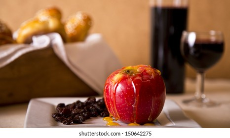 An apple drizzled with honey and raisins in a plate representing the sweetness of Rosh Hashanah