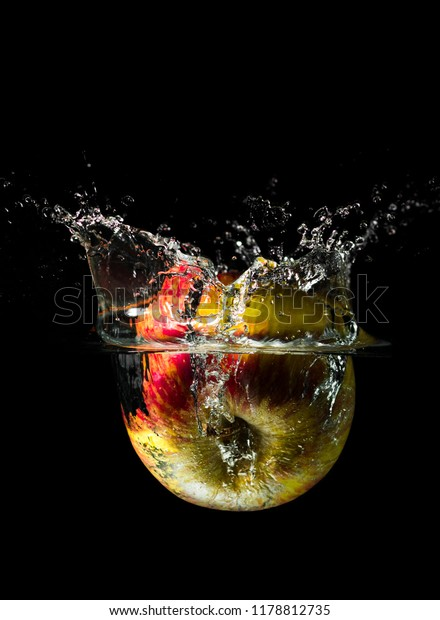 An apple dropped into liquid creating a beautiful splash