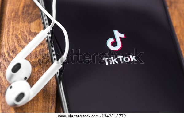 Apple Earpods and iPhone with TikTok logo on the screen. TikTok is app to create and share videos. Moscow, Russia - March 12, 2019