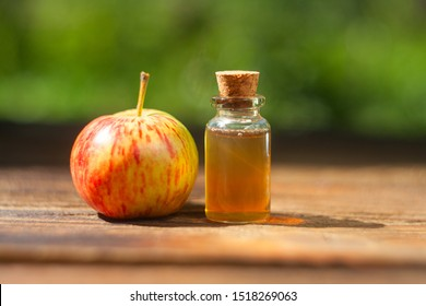 Apple essential oil in a beautiful bottle on the table