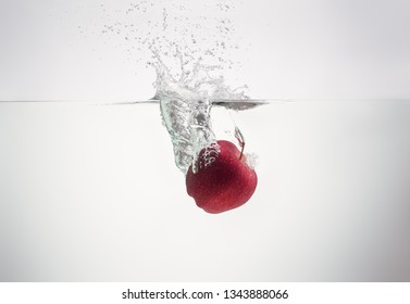 apple falls into the water scattering a lot of splashes and drops.