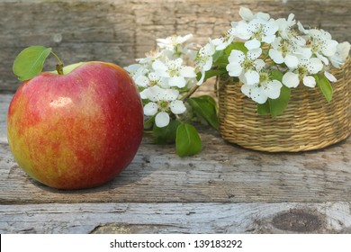 apple and flowers on wooden background