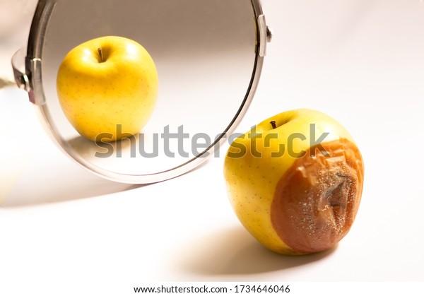 Apple en buen estado se mira en el espejo mientras su espalda está podrida. Concepto psicológico, engaño