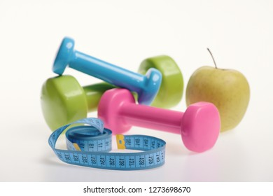 Apple and green, pink and blue barbells next to cyan measure tape, close up. Dumbbells near green apple on white background. Fit shape and sport concept. Health regime and fitness symbols.