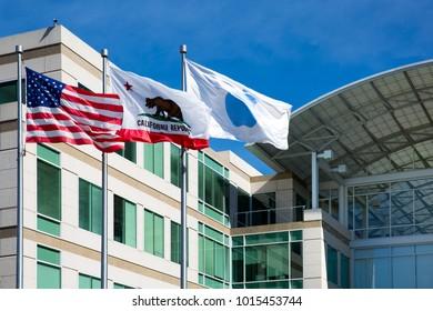 Apple Infinite Loop, Cupertino, California, United States (USA) - January 30, 2017: Three flags (Apple flag, California flag, Usa flag) in front of the Apple world headquarters at One Infinite Loop