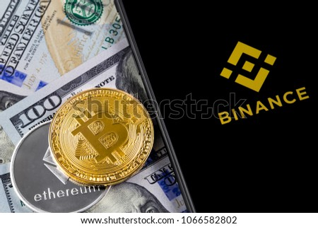 Apple iPhone and Binance logo and bitcoin, ethereum and dollars. Binance is a cryptocurrency exchange. Ekaterinburg, Russia - April 11, 2018
