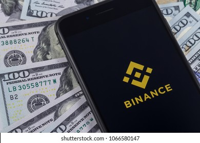 Apple iPhone and Binance logo, and dollars. Binance is a cryptocurrency exchange. Ekaterinburg, Russia - April 11, 2018