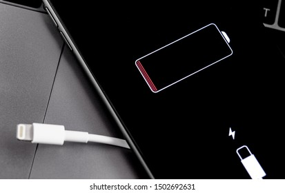 Apple iPhone smartphone with Lightning cable and battery logo on the display. Apple is a multinational technology company that designs, develops, online services. Moscow, Russia - July 12, 2019