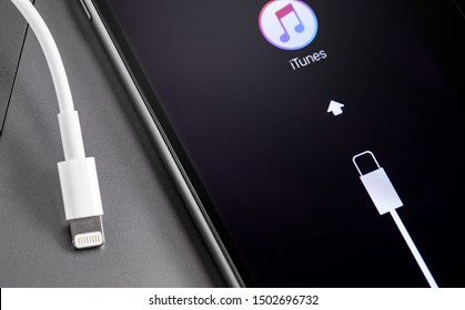 Apple iPhone smartphone with Lightning cable, iTunes logo on the screen. Apple is a multinational technology company that designs, develops, online services. Moscow, Russia - July 12, 2019