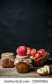 Apple jam in jar and fresh red apples outdoors