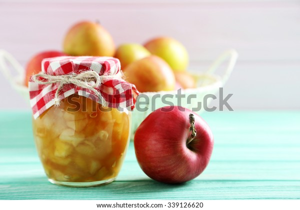 Apple jam in jar on a mint wooden table