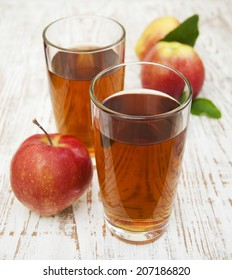 Apple juice and fresh apples on a wooden background