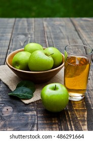 Apple juice glass with healthy green apples in wooden bowl. Outside in garden