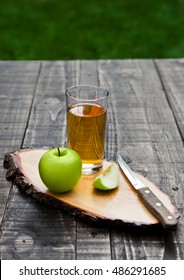 Apple juice glass with healthy green apples on kitchen board. Outside in garden