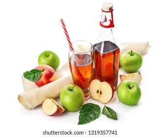 Apple juice in glass with straw and bottle with green leaves and napkin. Fruity still life, isolated on white background.