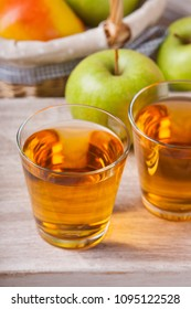 Apple juice in glasses and apples in a wicker basket on wooden table