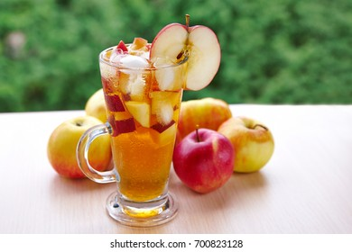 Apple juice with ice against the natural background of foliage