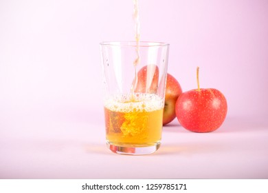 Apple juice poured into a glass of apples lie next