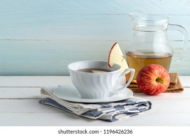 Apple juice or apple tea in white cup on wooden background.
