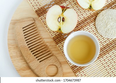 Apple juice (vinegar) and wooden hair brush. Ingredients for preparing homemade hair mask or face toner. Natural beauty treatment recipe and zero waste concept. Top view, copy space.