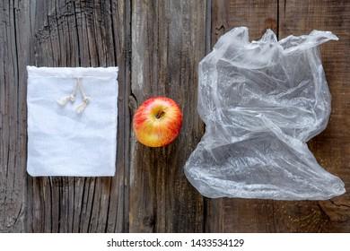 Apple lies between Reusable cotton produce bag and disposable plastic bag. Zero waste eco friendly concept