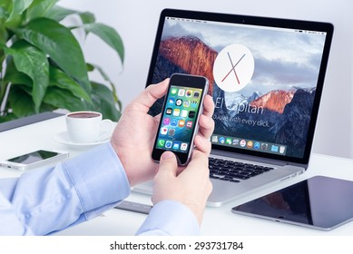 Apple MacBook Pro Retina with announced on WWDC 2015 OS X El Capitan on the screen and Apple iPhone 5s with iOS 9 on the display in male hands in office workspace. Varna, Bulgaria - May 29, 2015.