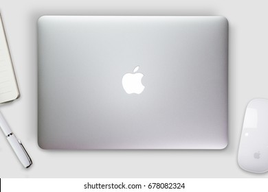 Apple Macbook Pro Retina cover on a desk, table with mouse and stationery. Mockup for decal, sticker design. Trendy office, freelance workplace, top view. White background.