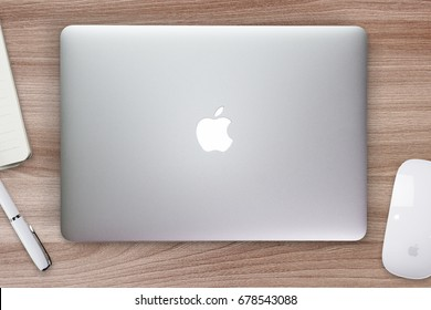 Apple Macbook Pro Retina cover on a desk, table with mouse and stationery. Mockup for decal, sticker design. Trendy office, freelance workplace, top view. Wooden background.