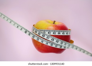 apple with a measering tape isolated on pink background