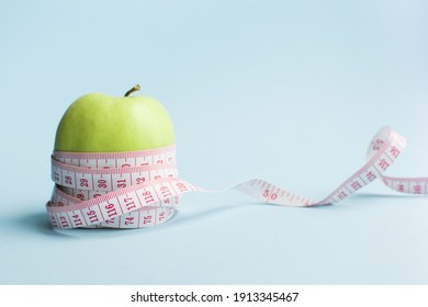 Apple with measuring tape on blue background. Weight loss, counting calories and healthy eating concept - calculate daily nutrition intake. Copy space.