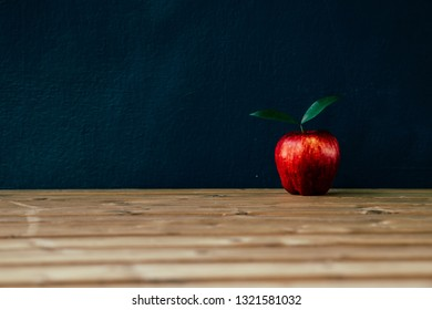 Apple on the desk in front of blackboard