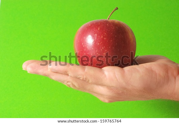 An Apple on the Hand on a Colored Background
