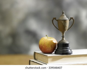 apple on a stack of books with a trophy