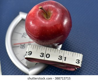Apple on Weighing machine with inch tape, concept of eating healthy and maintaining good Body Mass Index