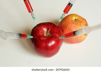 Apple and Orange with syringes. Genetically modified food.