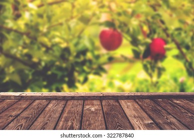 Apple orchard background, wood table for product placement, selective focus, retro toned image