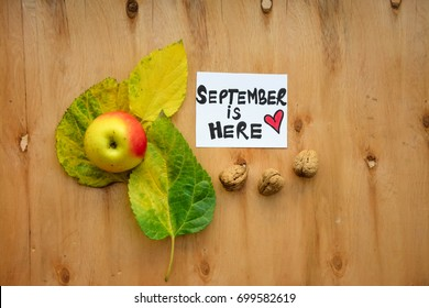 An apple over autumn leaves and September is here text on a note on wooden table