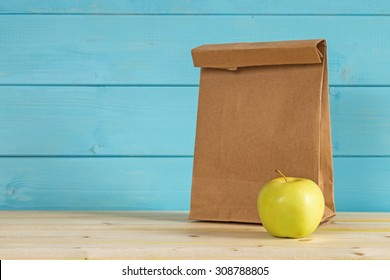 Apple and a paper bag for lunch on a blue rustic wooden background.