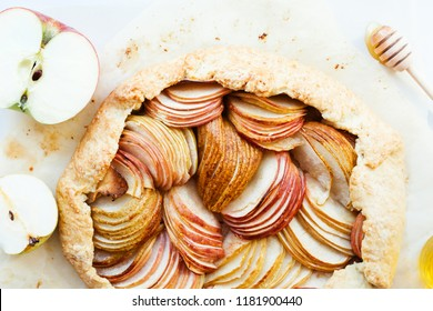 Apple and pear tasty galette with honey on the table. Open autumn pie, top view.