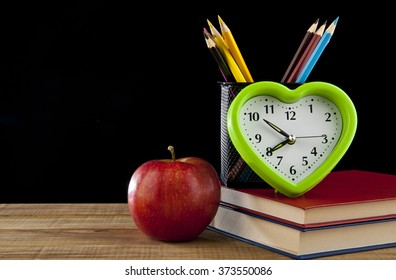 Apple, pencils, books and clock on black background