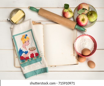 Apple Pie Baking Ingredients with Blank Recipe Book Page, rolling pin, vintage kitchen towel, butter and eggs on distressed white shiplap table background.  Horizontal flat lay view with copy space.