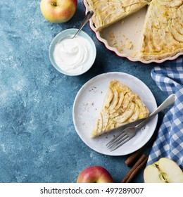 Apple pie with cream and cinnamon sticks on a blue background. Top view. Copy space